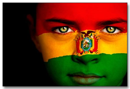 Portrait of a boy with the flag of Bolivia painted on his face.